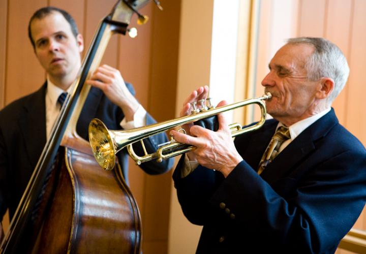 A man playing an upright acoustic bass and a man playing trumpet perform.