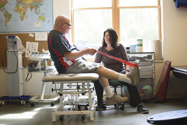 In a sunny gym room, a physical therapist encourages at a man using a red elastic band to do a leg exercise.