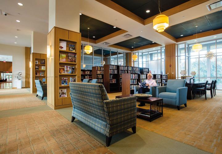 A NewBridge on the Charles resident sits and reads a magazine in a contemporary library with ample seating and open shelving for books and periodicals.