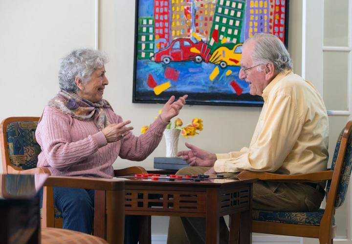 An older man and woman at Center Communities of Brookline play a game of checkers, near a brightly colored painting of city life.