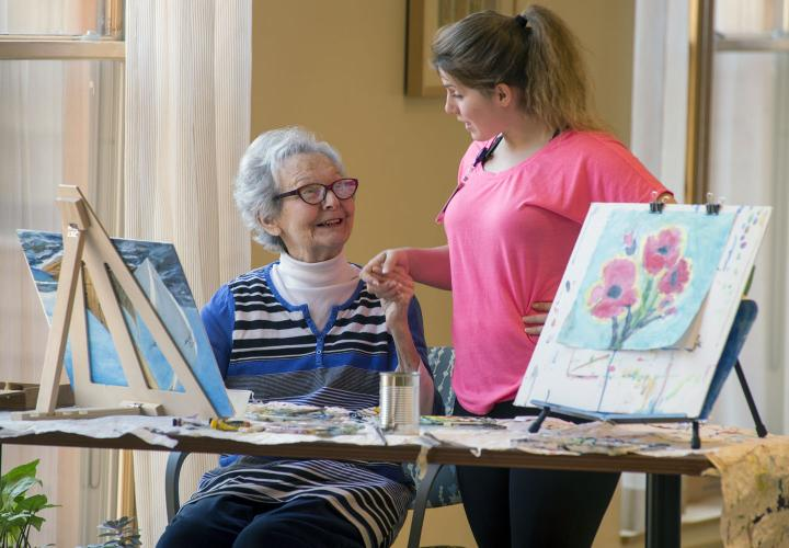 An older woman sits at a table painting at Hebrew Rehabilitation Center in Dedham, with bright artwork in the foreground. She is smiling up at a younger female staff member who is standing next to her and holding her hand.