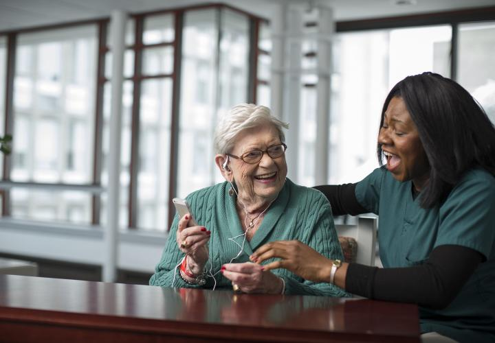 An older woman listens to an iPod. A staff caregiver has her arm around the woman. They're both laughing.