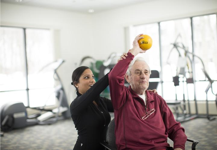 A senior holds a ball above his head with the help of a physical therapist in the Simon C. Fireman Community fitness center.