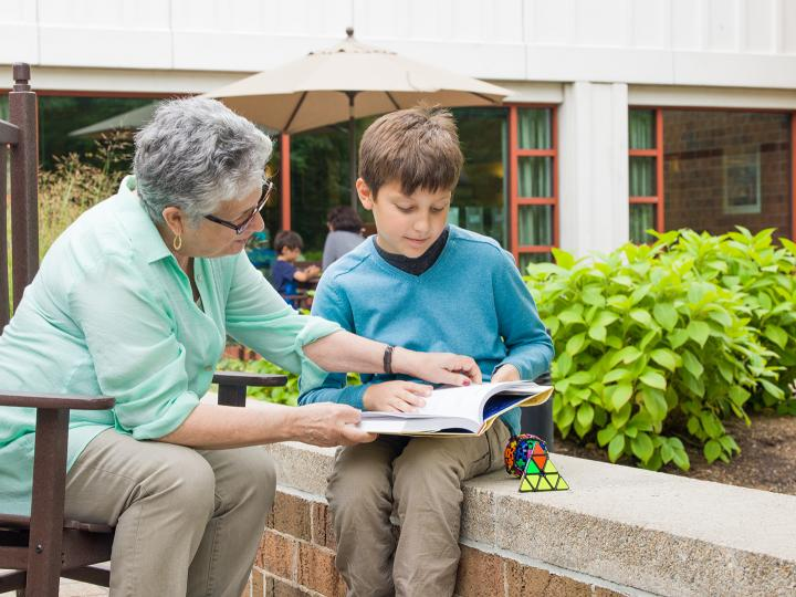 An Orchard Cove resident helps a local student during a tutoring session.