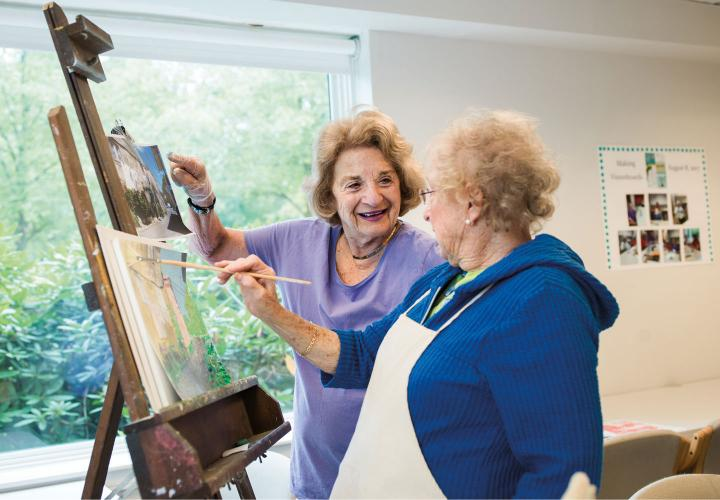 Two Orchard Cove residents stand at an easel, discussing a painting in progress, in a sunny art studio.