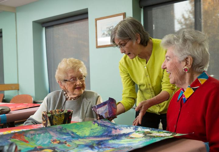 Residents looking at painting with staff member