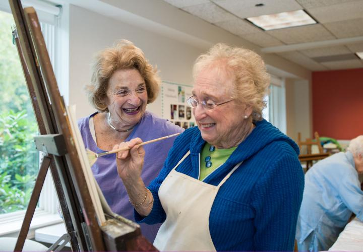 A resident chats with another resident painting on a canvas.