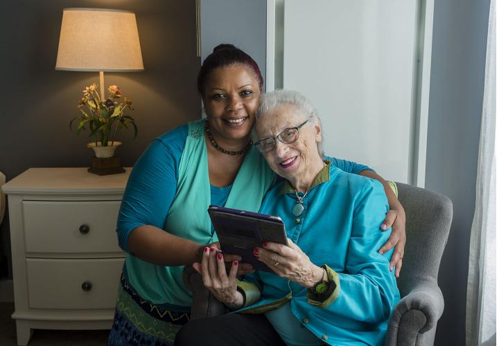 Smiling caregiver with arm around older adult woman who is smiling and holding an iPad