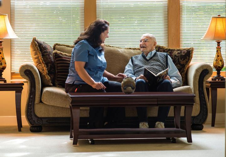An older man laughs with a nursing assistant in a well-furnished living room.