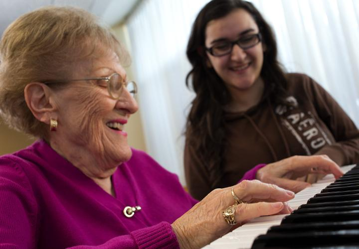 Older woman in pink sweater plays a duet on piano with a high school student