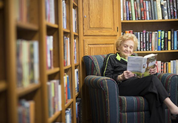 A woman sits in an easy chair, smiling, reading a book, surrounded by walls of bookshelves.