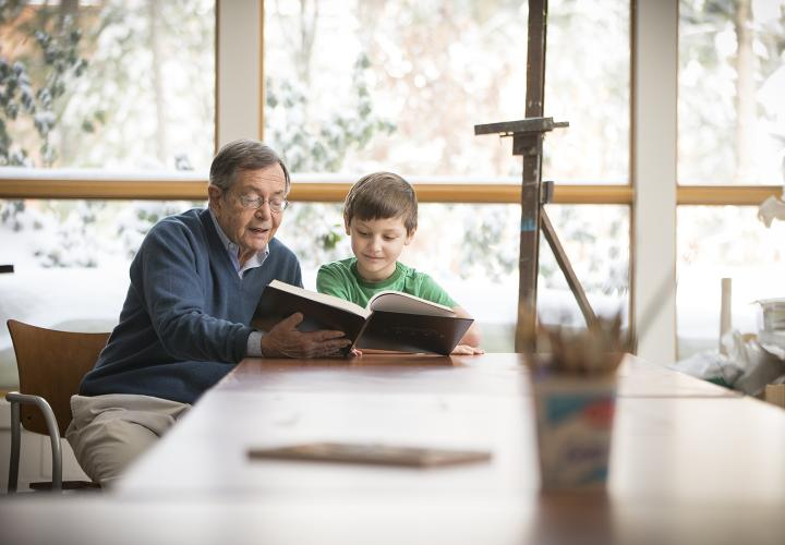 Older man in blue sweater and grade-school student in green t-shirt read through a large book together.