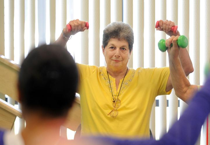 Two Simon C. Fireman Community residents lifting weights in an exercise class with instructor