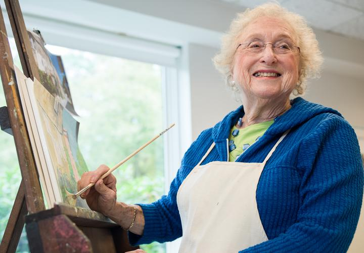 Older woman in blue sweater paints at an easel in a sunny art studio.