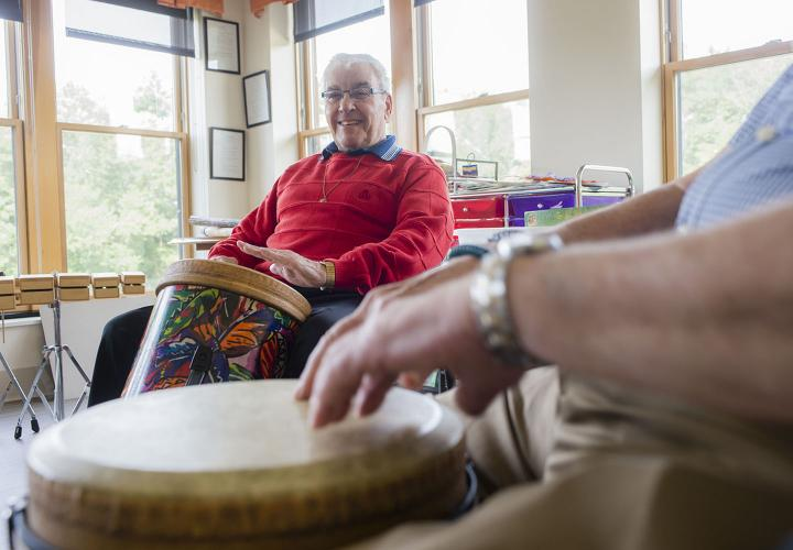 Older adults participate in a drum circle
