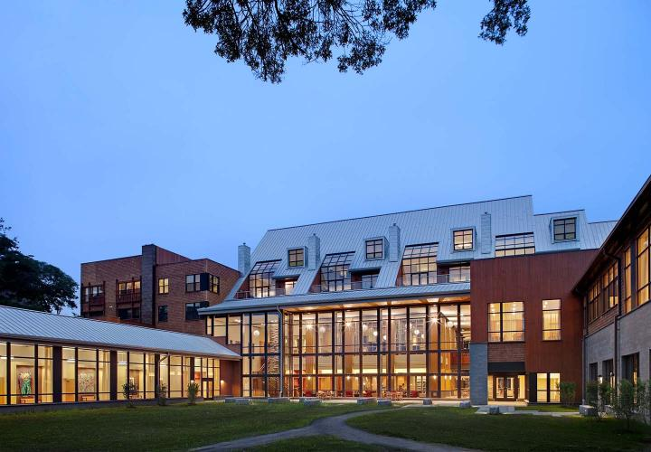 An exterior view of the Shapiro Community Center at NewBridge on the Charles at dusk, with multi-story windows revealing contemporary décor within.