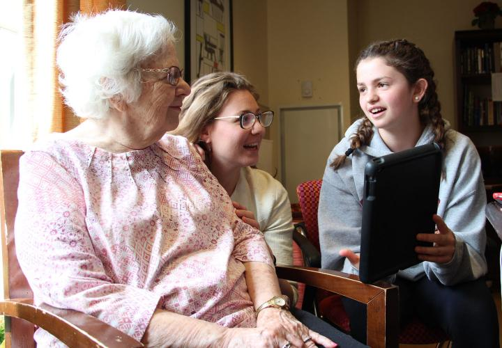 An eighth grader with braided pigtails holds up a tablet as she shares a conversation in Spanish with a memory care patient.