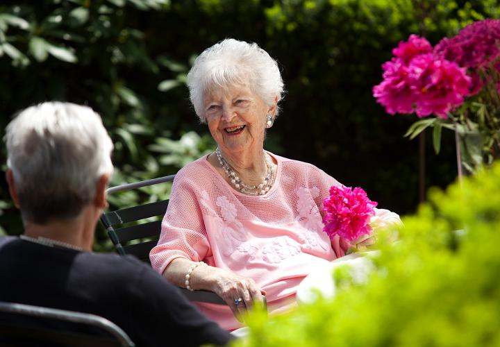 Older woman in garden laughing with friend