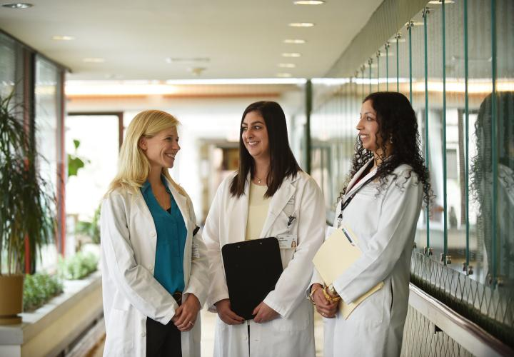 Three female doctors from the Harvard Medical School geriatric fellowship standing in a hall at Hebrew Rehabilitation Center in Boston.