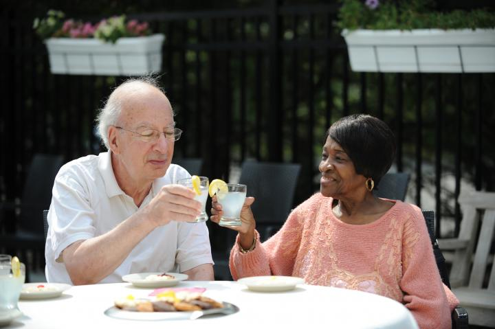Two adult day health participants raise glasses in a toast to the newly opened patio in Roslindale.