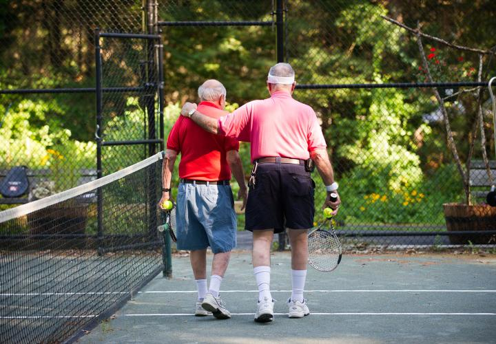 Two older men in colorful T-shirts share a moment as they walk off the tennis court after a game on the Orchard Cove campus.