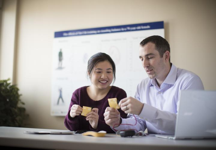 A female and a male researcher from the Hinda and Arthur Marcus Institute for Aging Research sit at a table with a laptop. They are each holding a small yellow square that has wires attached.
