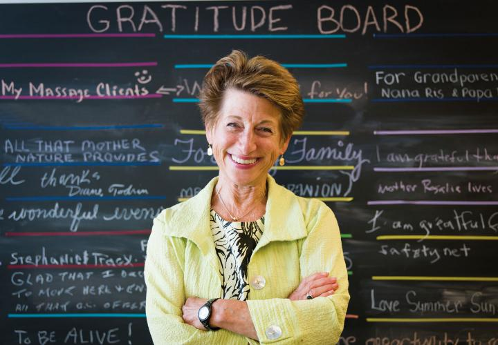 Vitalize 360 Coach stands in front of gratitude board created by residents.