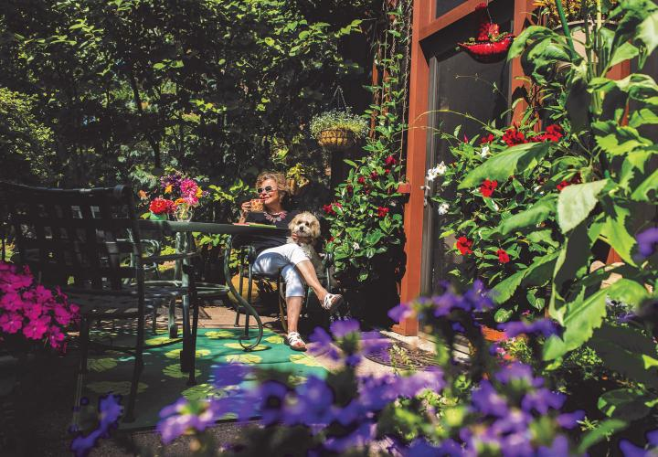A NewBridge resident enjoys a cup of coffee on her garden patio, with pet dog on her lap.
