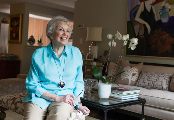 A smiling Orchard Cove resident in a turquoise shirt sits on a couch in her well-appointed independent living apartment.