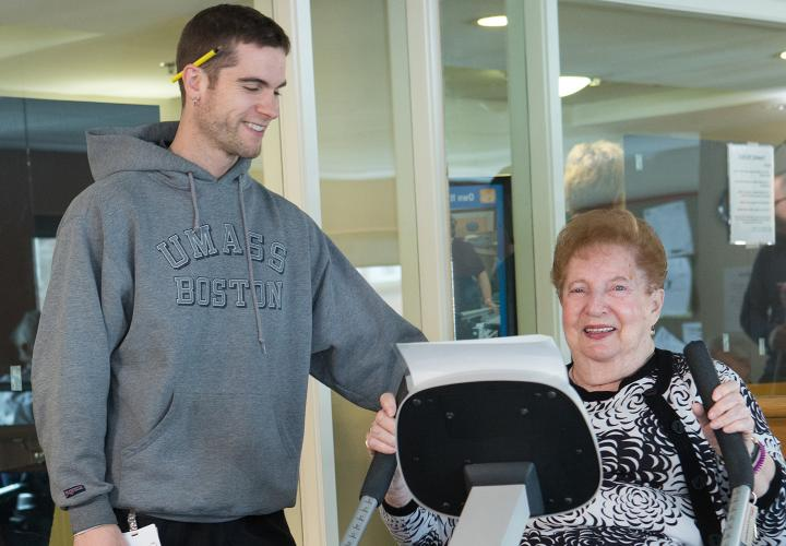 Hebrew SeniorLife fitness trainer helps an older woman exercise on a machine designed for geriatric fitness.