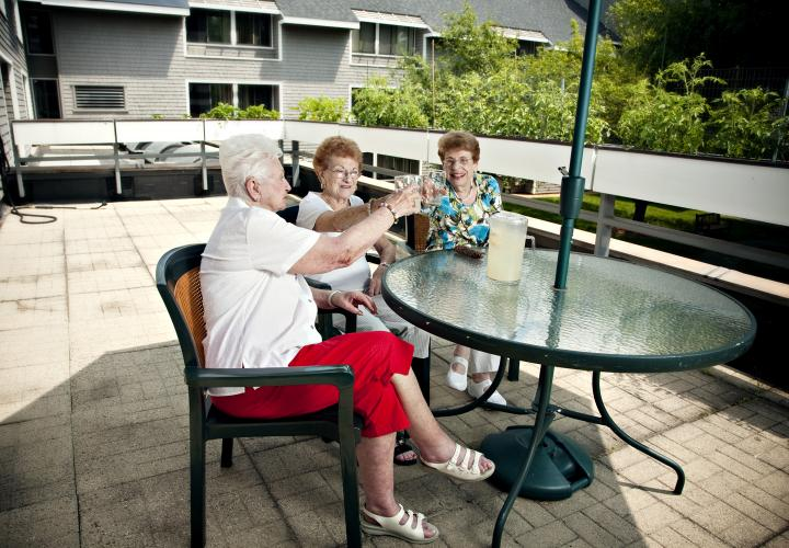 Three older women sit outdoors at a patio table, smiling and toasting with lemonade.