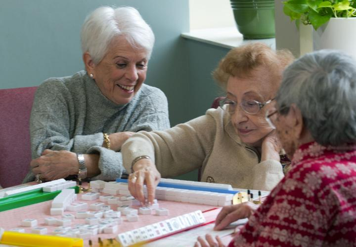 A volunteer sits at a table playing mah jong with Hebrew Rehabilitation Center patients.