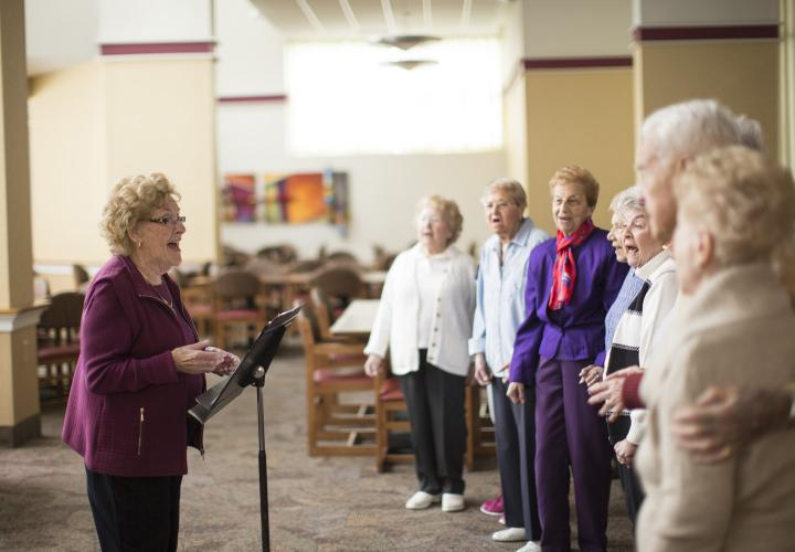 Group of older adults singing in front of a choir director in an open room at Jack Satter House.