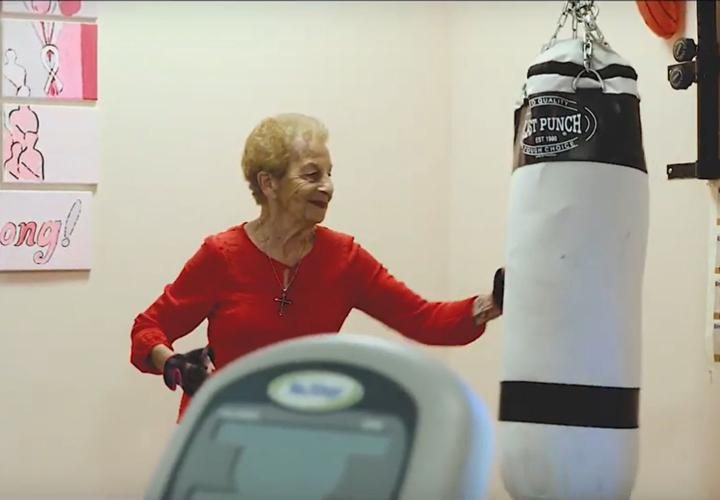 Jack Satter House resident Marge Marino punches a punching bag in the community's fitness center.