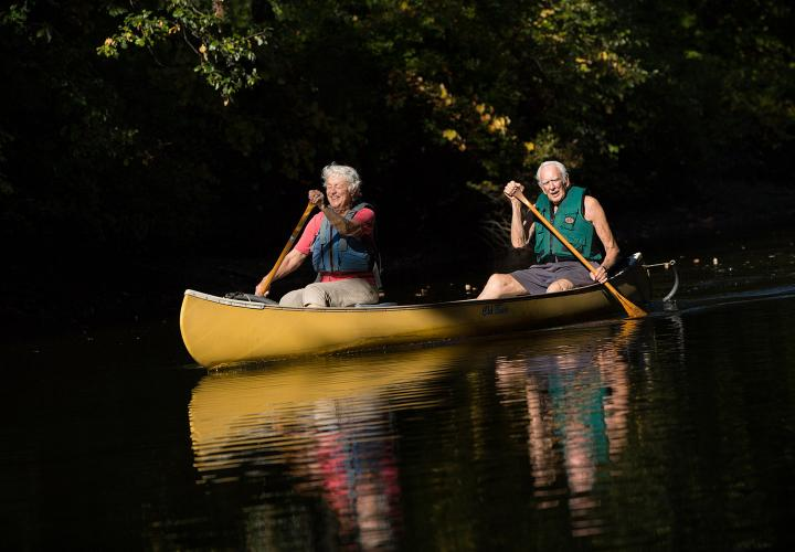 An older couple enjoys an afternoon of canoeing on the Charles River thanks to the NewBridge on the Charles boat launch connecting the campus to the Dedham Water Trail.