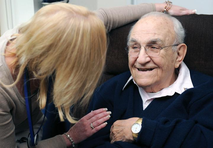 Older man seated and smiling as he speaks with a Hebrew SeniorLife hospice nurse.
