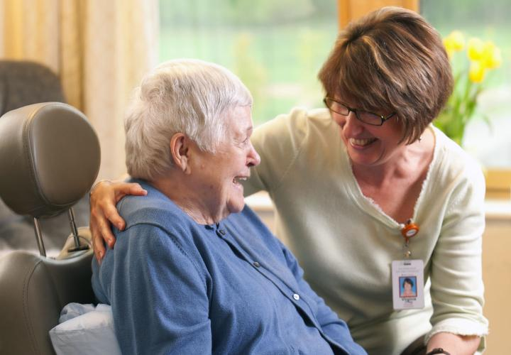 A long-term chronic care patient in a wheelchair smiles at her caregiver.