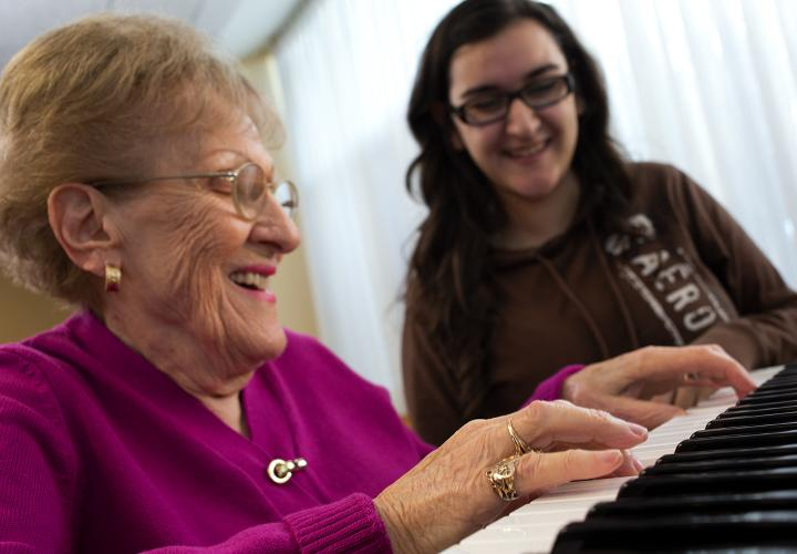 Older woman playing piano with a volunteer.