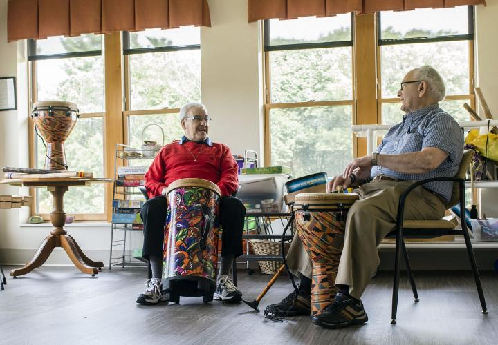 Two residents of memory care assisted living at NewBridge on the Charles enjoy some drumming time in the studio.