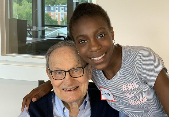A school-age girl and a senior living resident enjoy their time participating in an intergenerational program.