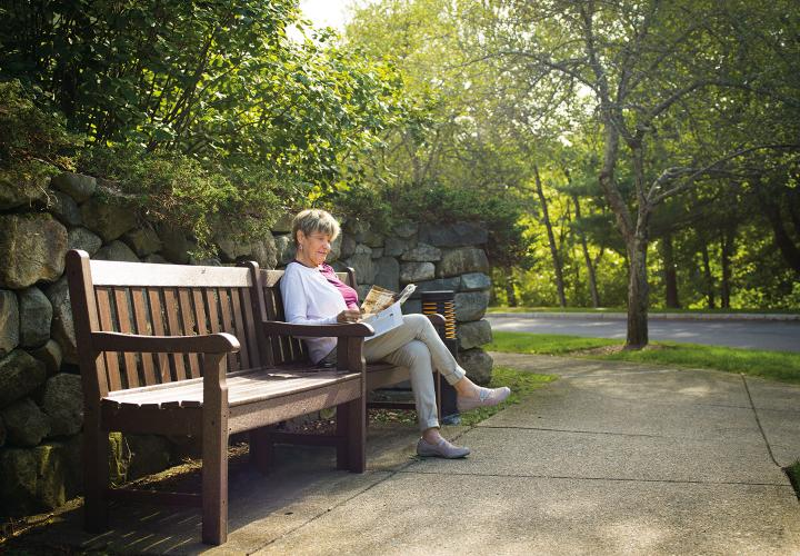 A female Orchard Cove resident sits on a bench and reads