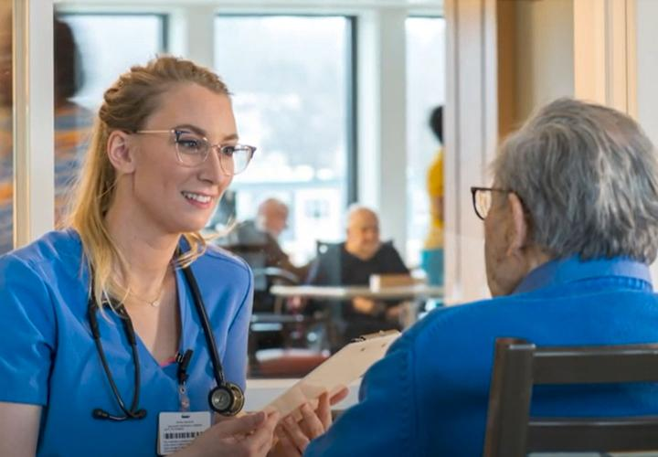 A therapist smiles as she talks to a Hebrew Rehabilitation Center patient.