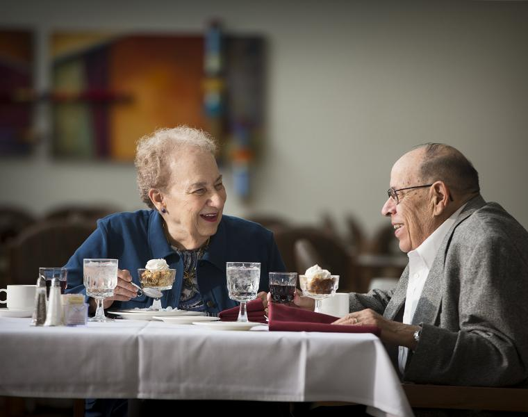 An older man and woman are seated at a restaurant table, smiling and looking at each other. There is dessert in front of them and the woman is holding a spoon.