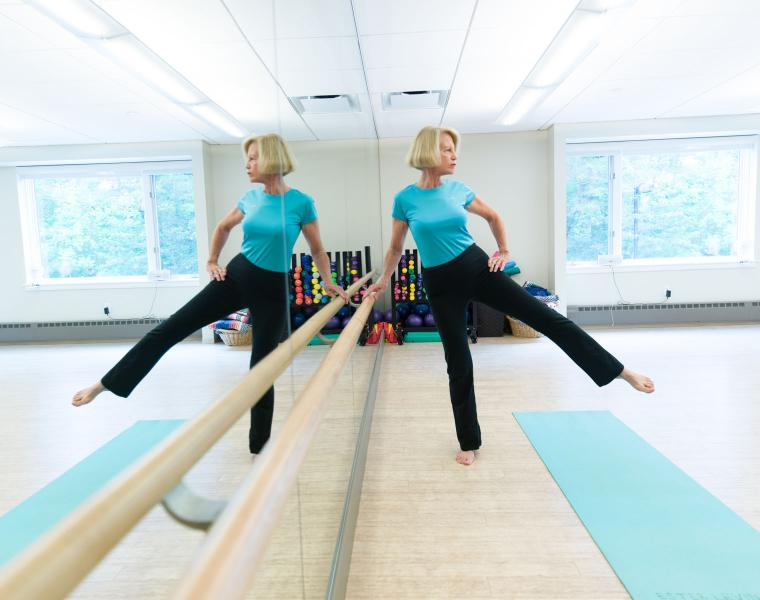 An Orchard Cove resident stretches in a mirrored exercise studio.