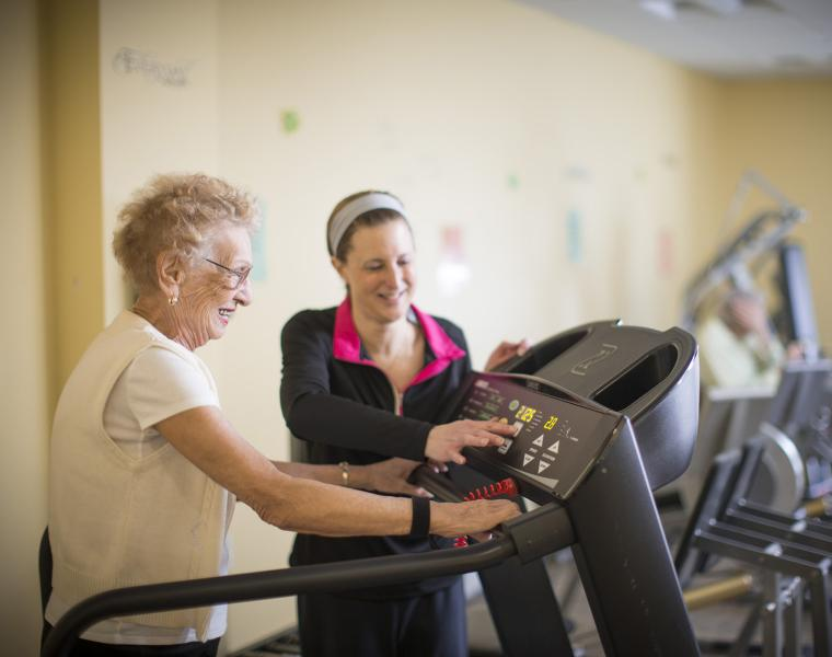 An older woman is walking on a treadmill. A younger woman in workout clothes stands next to her, changing the display on the treadmill. They are both smiling.